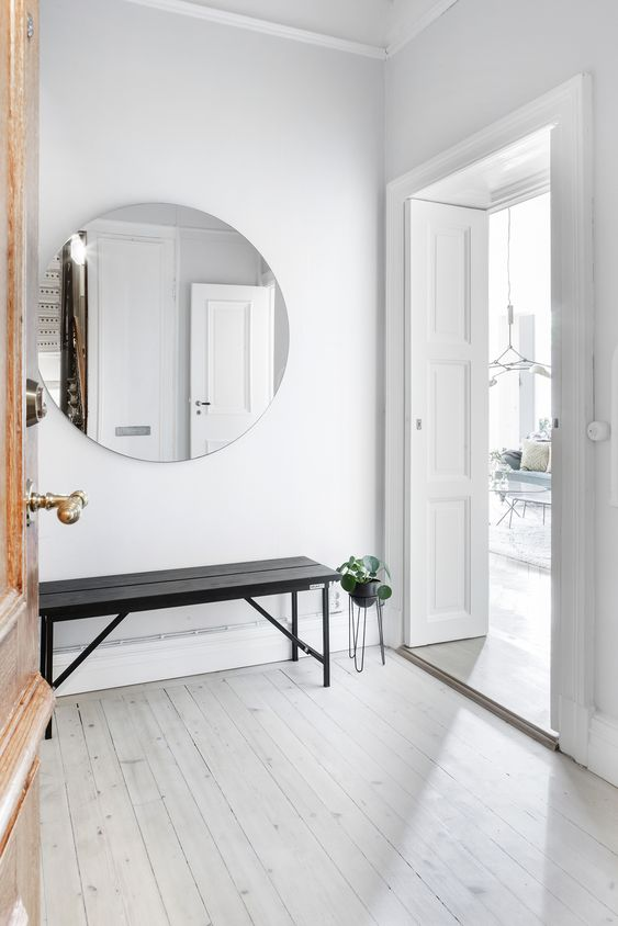 a mirror is a must for an entryway and it makes a space larger, which is essential for a small space