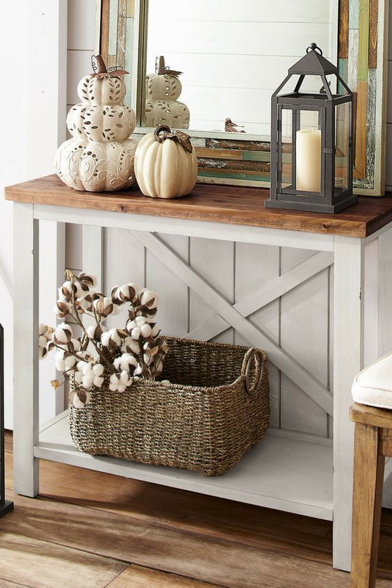a vintage rustic console with laser cut pumpkins and a porcelain one, a candle lantern and a basket with cotton branches