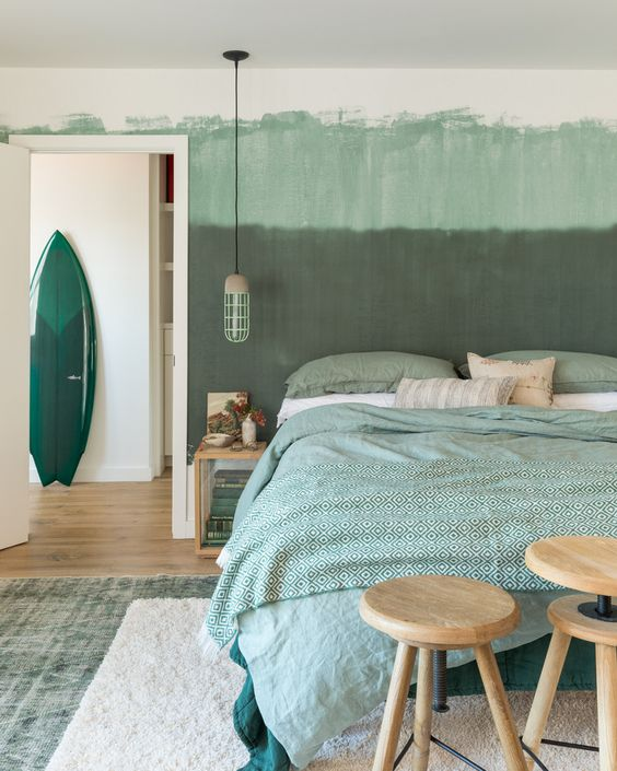 an ombre green statement wall and green printed bedding for a relaxing and comforting feel