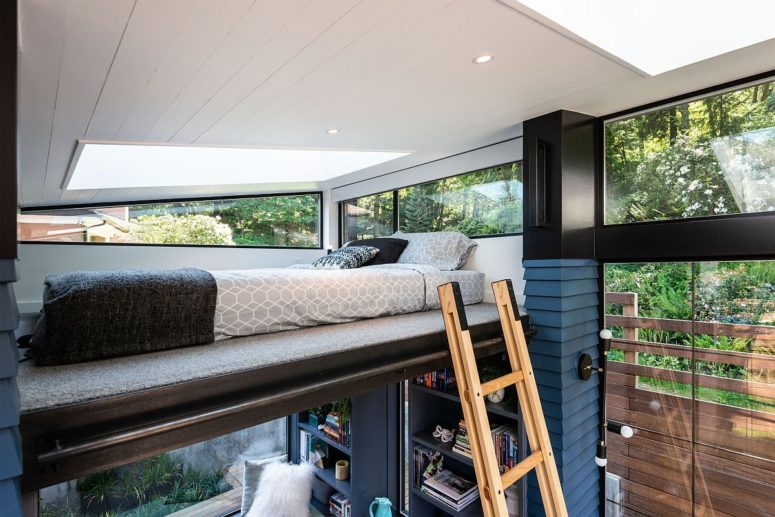 A ladder invites to a small sleeping space up, a bed with a skylight and windows on each side