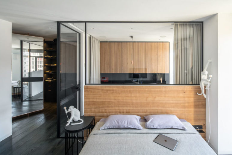 The bedroom is separated from the rest of the spaces with glass partitions