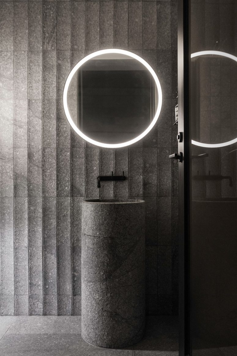 The sink is a free-standing stone one, and the mirror is lit up