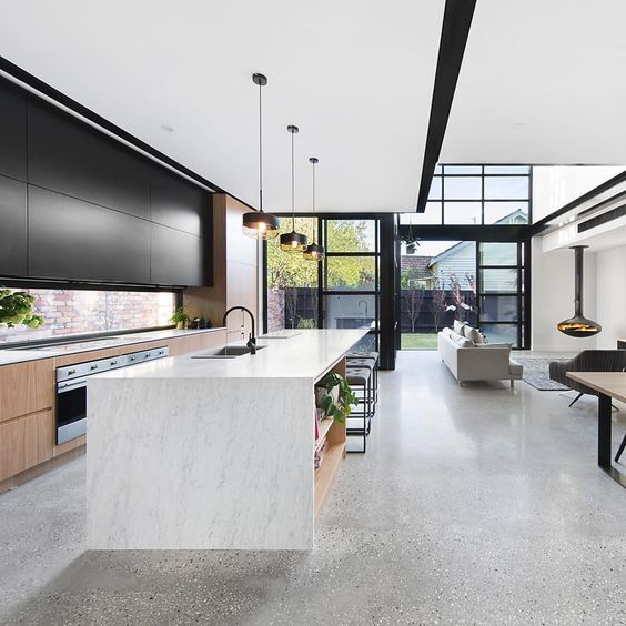 a statement point is sleek black upper cabinets of the kitchen, the color is echoed in other elements of the space, too