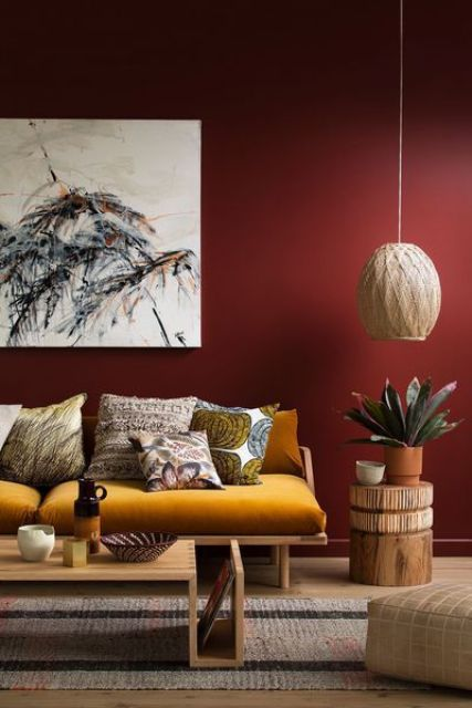 a stylish living room with a burgundy accent wall as a dominant feature and a saturated yellow sofa