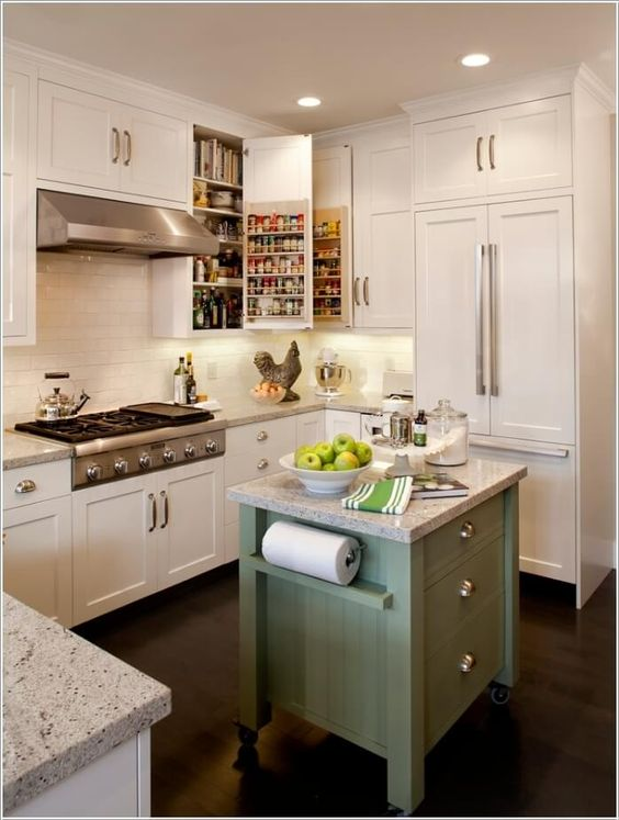 a tiny green kitchen island on casters with drawers and holders plus a stone countertop