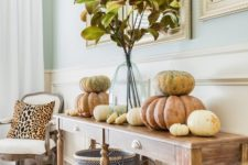 09 a vintage farmhouse console table with chevron baskets, natural pumpkins stacked on each other and fall leaves in a vase