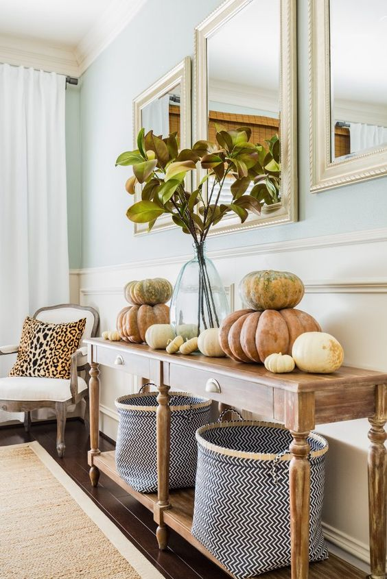 a vintage farmhouse console table with chevron baskets, natural pumpkins stacked on each other and fall leaves in a vase