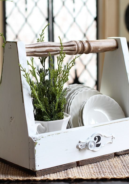 a vintage farmhouse dish caddy of white and stained wood with plates and planted greenery