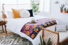 09 a wicker bench at the foot of the bed, colorful bedding and large tassels hanging