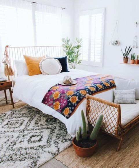 a wicker bench at the foot of the bed, colorful bedding and large tassels hanging