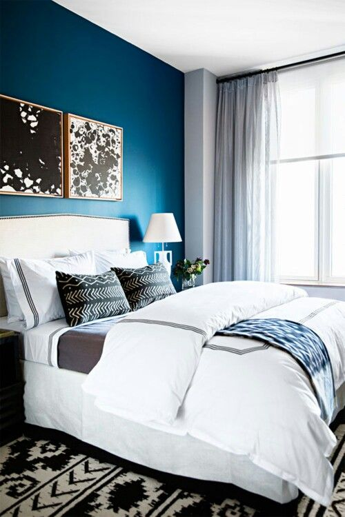 a monochromatic bedroom is infused with color - a bold blue accent wall that makes it vivacious