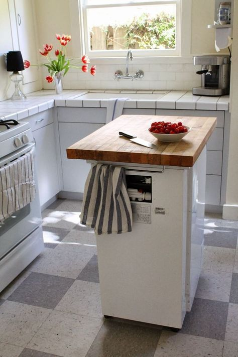 a portable dishwasher kitchen island with a butcher block countertop and holders is a functional option