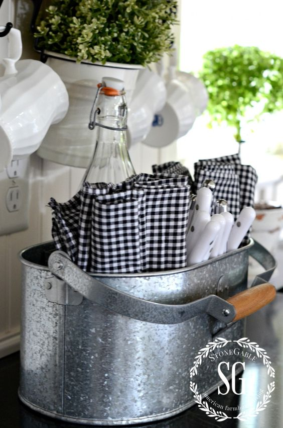 a rustic kitchen caddy of galvanized steel for cutlery and bottles
