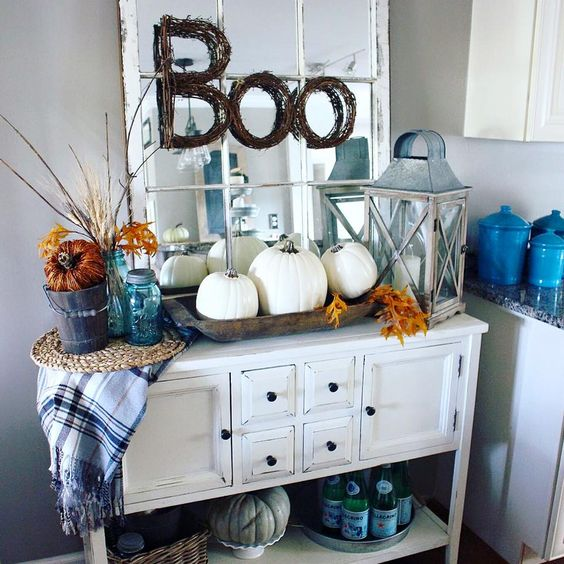 a vintage console with a trio of white pumpkins, fall leaves and a plaid blanket