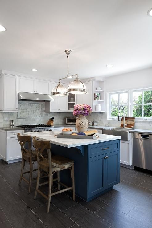 a beautiful white kitchen with a navy kitchen island and a marble countertop for a chic touch