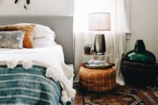 11 a boho rug, a leather ottoman, folksy pillows and a feather hanging for a cool boho look