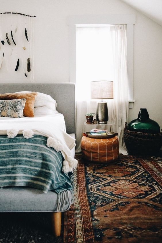 a boho rug, a leather ottoman, folksy pillows and a feather hanging for a cool boho look