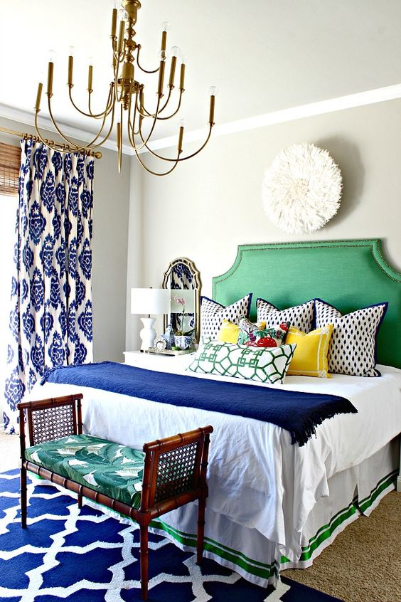 a bright green upholstered bed and a bold rattan bench with a palm leaf print