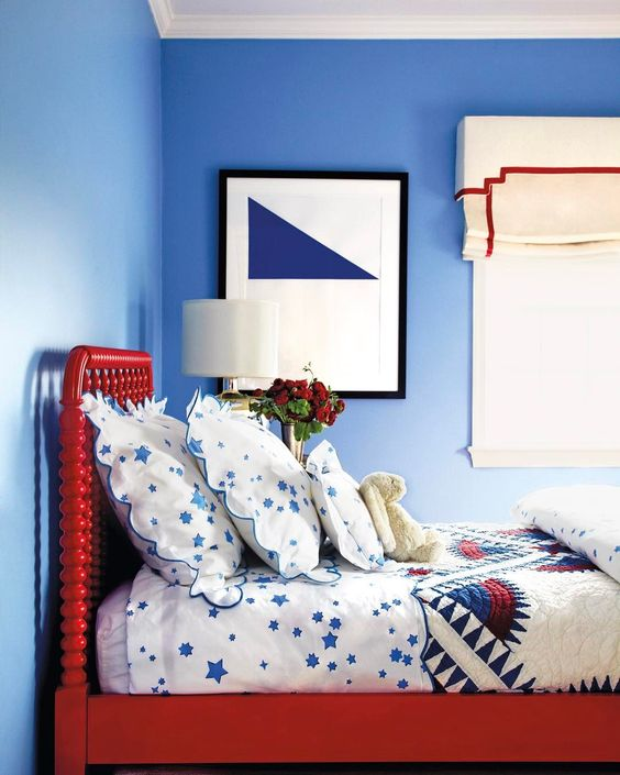 a bright red bed is a statement in a blue bedroom and an interesting color touch
