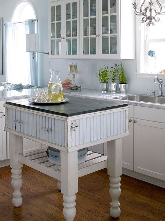 a farmhouse kitchen island in white and blue with drawers and a shelf for a coastal farmhouse kitchen