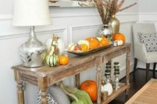 11 a rustic console table with pumpkin arrangements, pillows, blankets and dried blooms