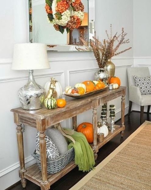 a rustic console table with pumpkin arrangements, pillows, blankets and dried blooms