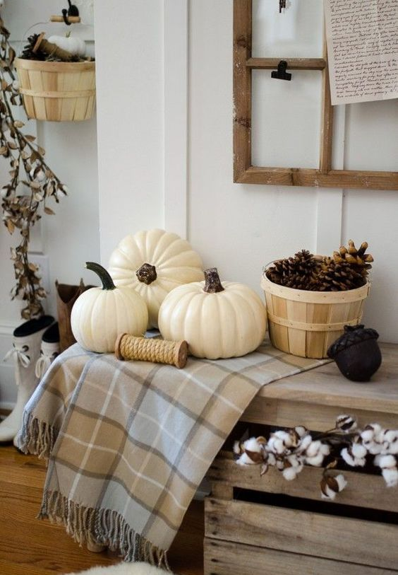 a simple display with a basket of pinecones, some white pumpkins and cotton in a pallet box
