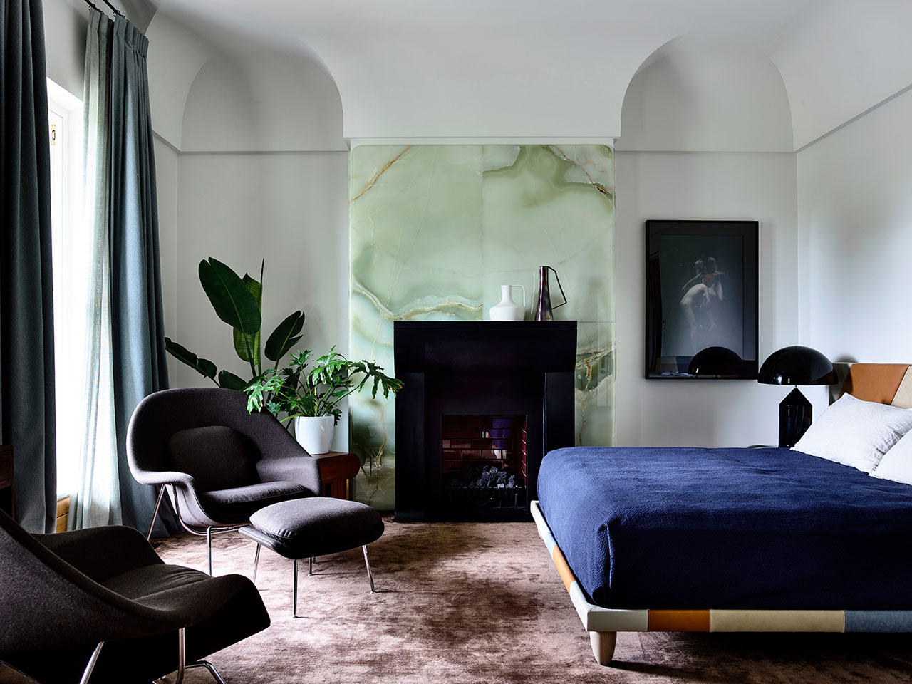 The master bedroom shows off a gorgeous green onyx wall, a built in fireplace and a bold bed