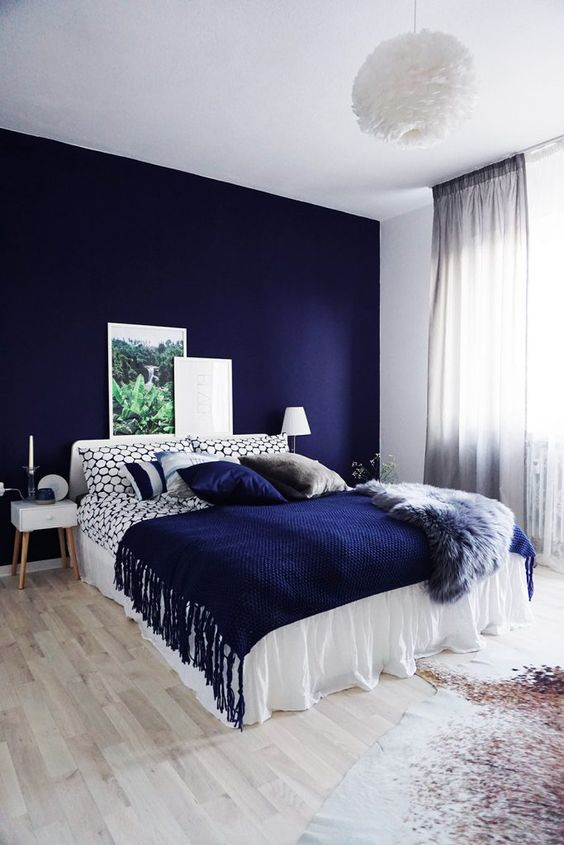 a bold blue accent wall plus a matching pillow and a fringed blanket for a wow effect