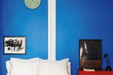 12 a bright red dresser in front of a blue wall make up a bold color combo for this bedroom