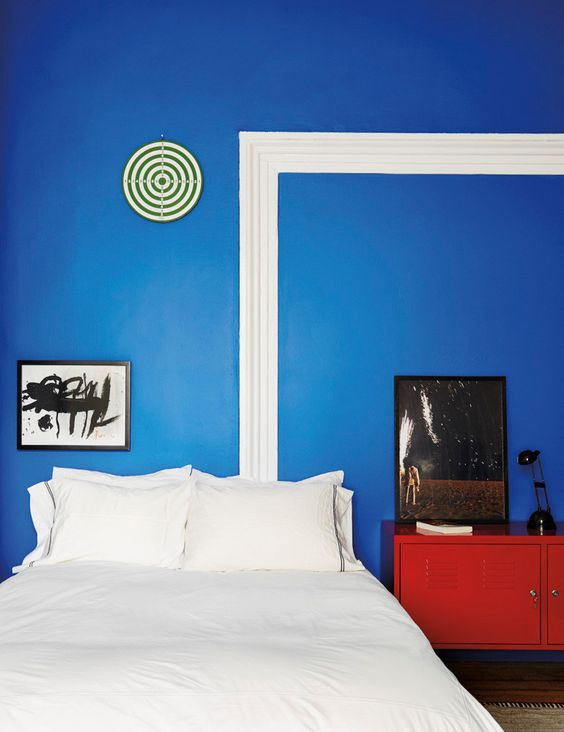a bright red dresser in front of a blue wall make up a bold color combo for this bedroom