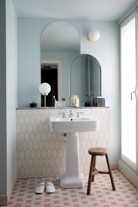 a pale blue wall and a creamy tile accent for a subtle and delicate look in your bathroom