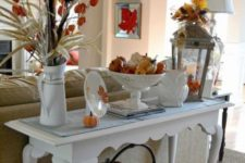 12 a refined console table with colorful pumpkins, fall leaves, porcelain and a metal basket with pumpkins