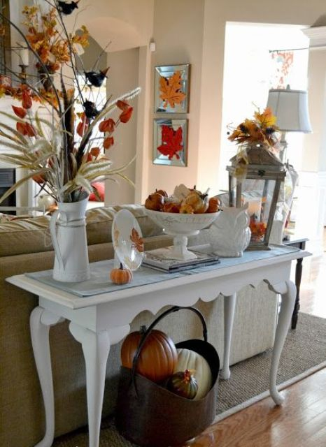 a refined console table with colorful pumpkins, fall leaves, porcelain and a metal basket with pumpkins