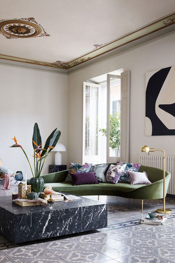 a refined curved green sofa on tall legs and a marble table are the center of the room