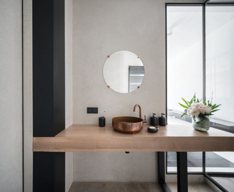 The chic wooden vanity is spruce dup with a copper sink and faucet