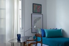 13 The guest bedroom features a comfy daybed, artworks and a vintage chair plus a modern desk