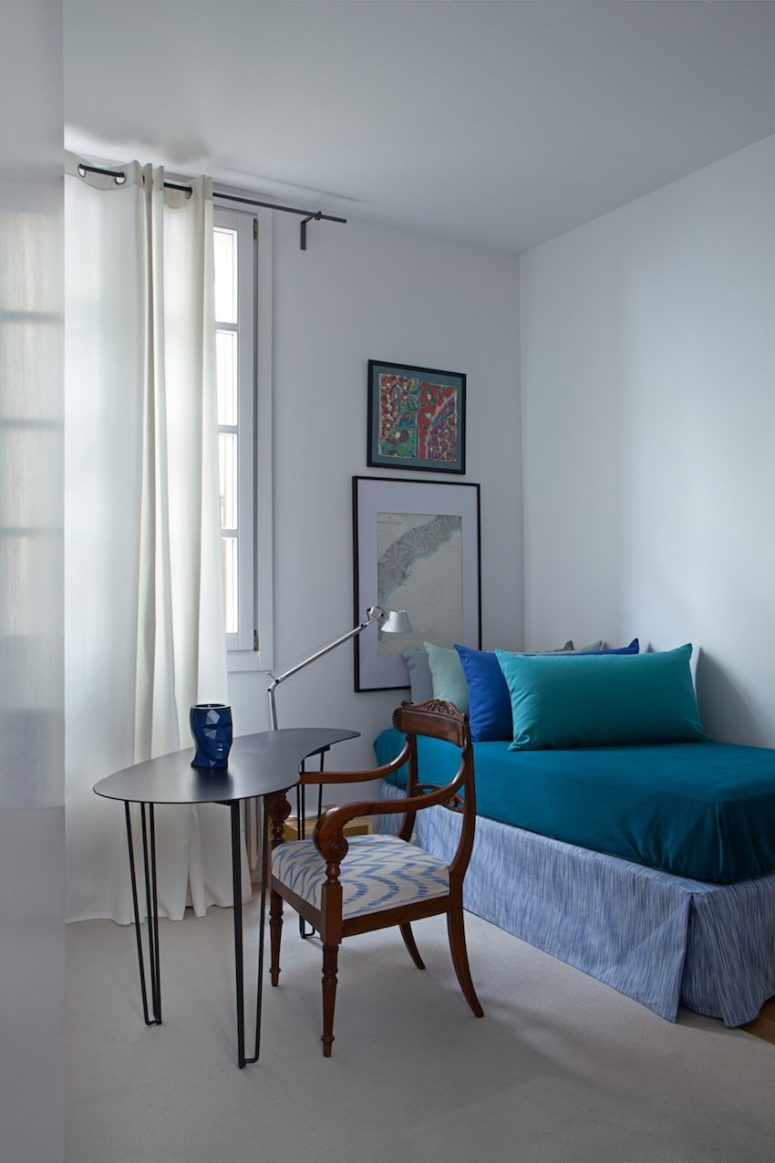 The guest bedroom features a comfy daybed, artworks and a vintage chair plus a modern desk