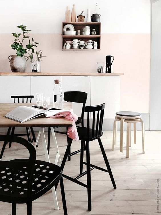a blush kitchen backsplash and white cabinets are highlighted with black furniture