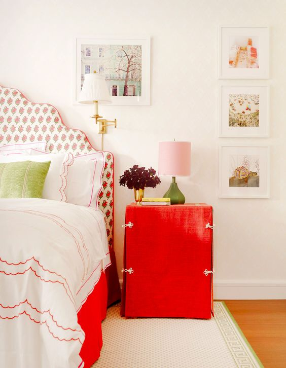a bright red nightstand and a red floral print upholstered bed for a cute touch