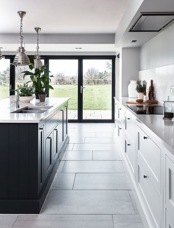 a contemporary kitchen with white cabinets and a black kitchen island plus the same countertops for both