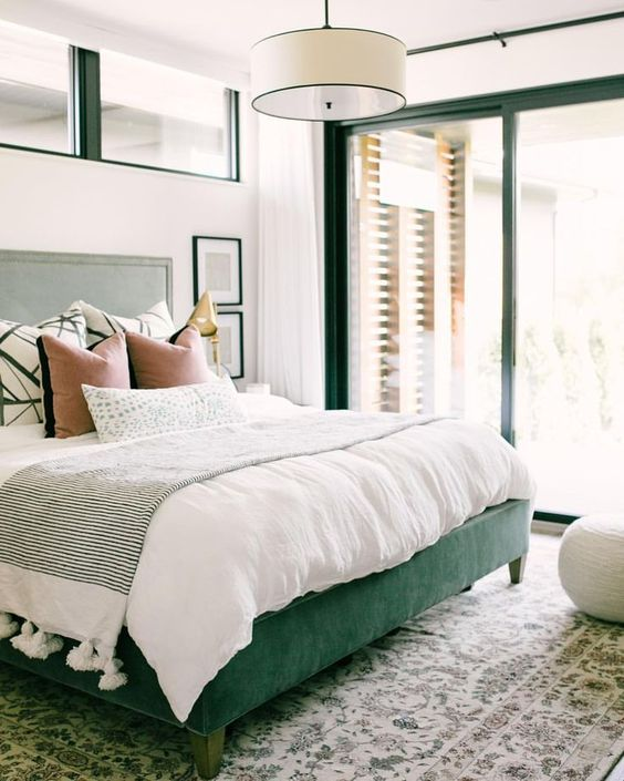 a green upholstered bed and matching framing of the windows and doors for a bold look