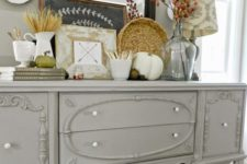 13 a grey farmhouse console table with faux pumpkins, acorns, nuts, wheat and dried flowers