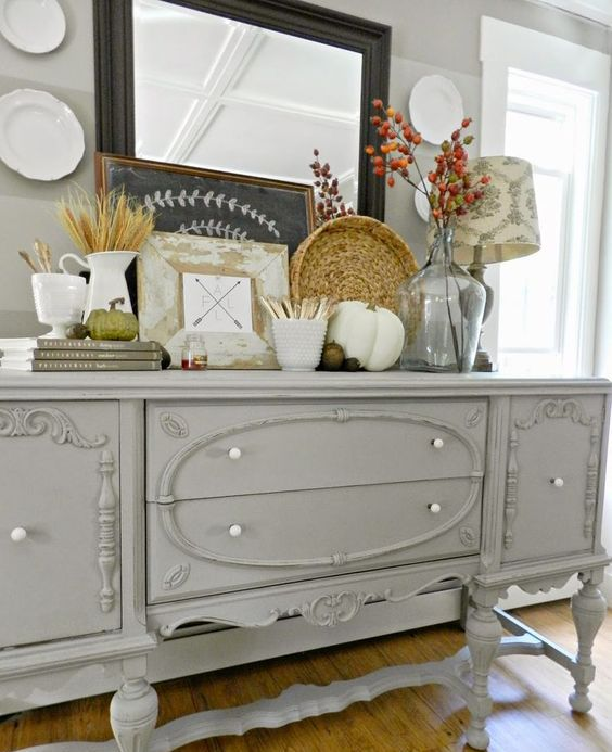 a grey farmhouse console table with faux pumpkins, acorns, nuts, wheat and dried flowers