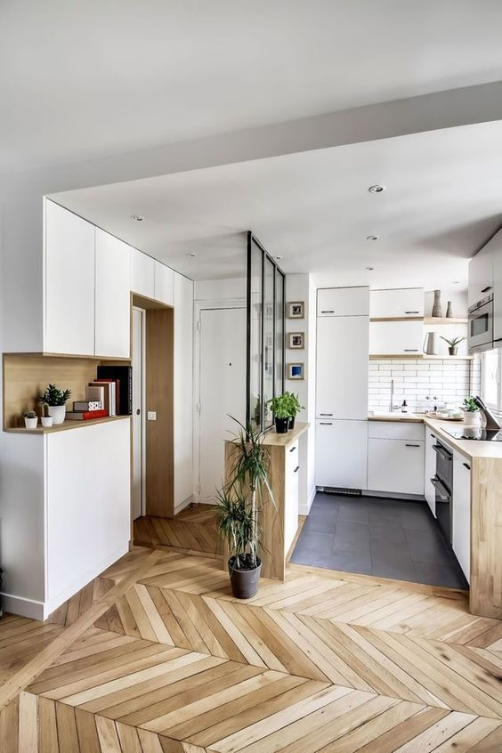 the kitchen and entryway seamleslly flow into each other thanks to the same colors and materials