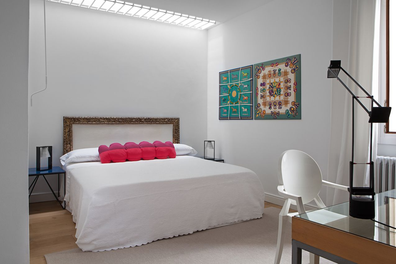 The unusual cushion provides the dominant pop of pink in this bedroom