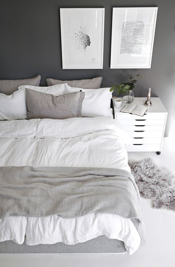 a bedroom in the shades of grey mixed with crispy white and spruced up with artworks