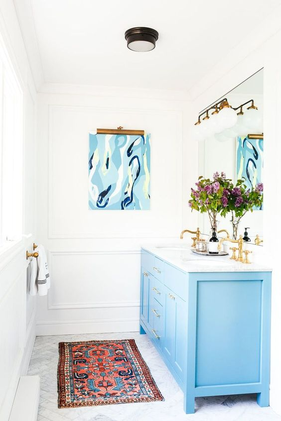 a blue bathroom vanity plus brass fixtures create a chic and refined feel in the bathroom