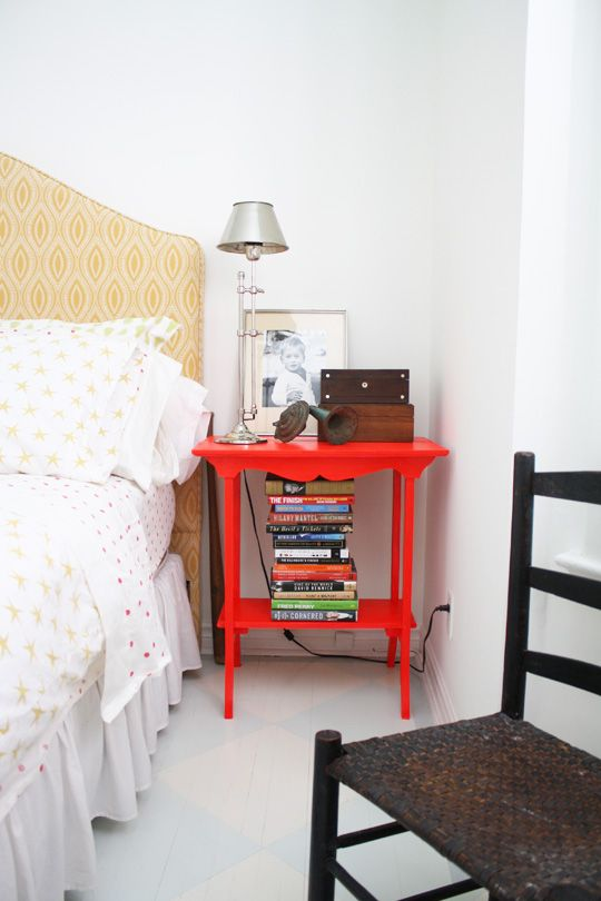 a bright red nightstand matches the bedroom style but adds a touch of super bold color
