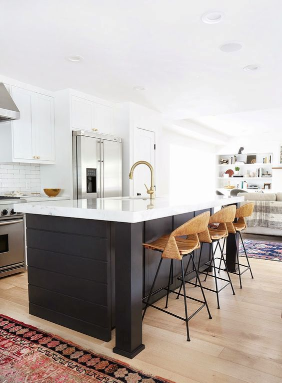 a contrasting black kitchen island with a sleek white countertop to connect it to the cabinets